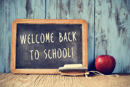 a chalkboard with the text welcome back to school written in it, a piece of chalk, an eraser and a red apple on a rustic wooden table, cross processed Stock Photo