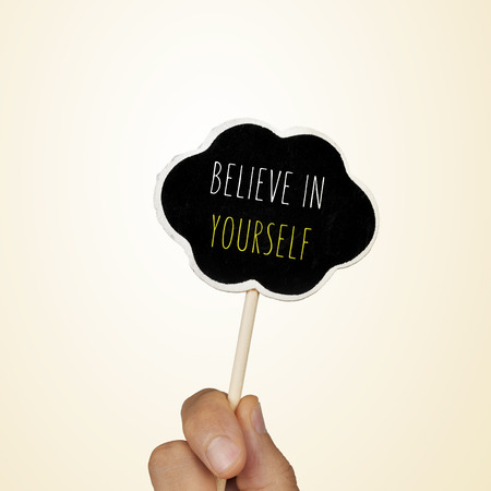 beliefs: closeup of the hand of a young woman holding a chalkboard in the shape of a thought bubble with the text believe in yourself written in it