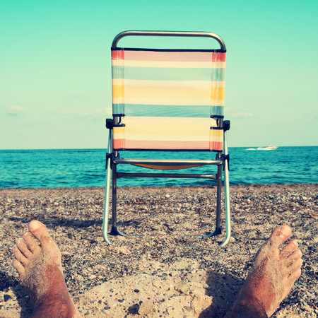 relaxing beach: closeup of the feet of a young caucasian man relaxing and a striped folding chair on the beach, with a filter effect