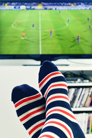 football socks: closeup of the feet of a man who is watching a soccer match in the TV, wearing striped socks
