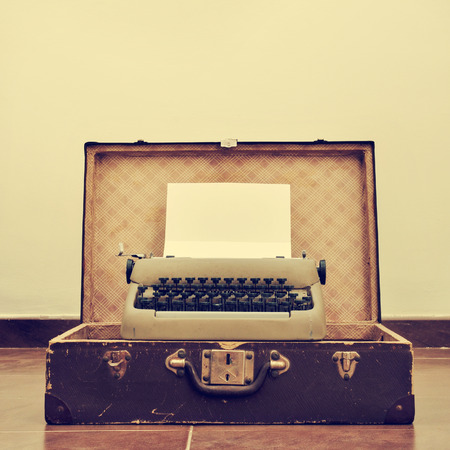 vintage typewriter: an old typewriter with a blank page in its roller, placed in an old suitcase, with a retro effect Stock Photo