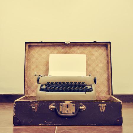 valise voyage: une vieille machine à écrire avec une page vierge dans son rouleau, placé dans une vieille valise, avec un effet rétro
