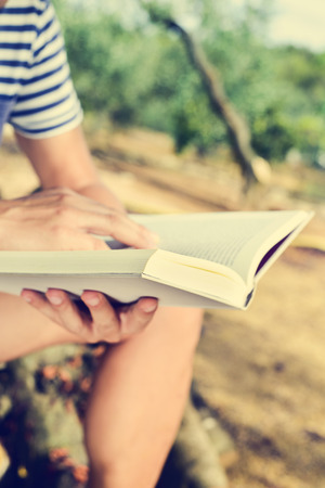 memoirs: closeup of a young caucasian man reading a book outdoors in a natural landscape in a sunny day Stock Photo