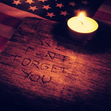 not forget: the sentence we do not forget you carved on wood and the flag of the United States and a lighted candle, with a filtered effect