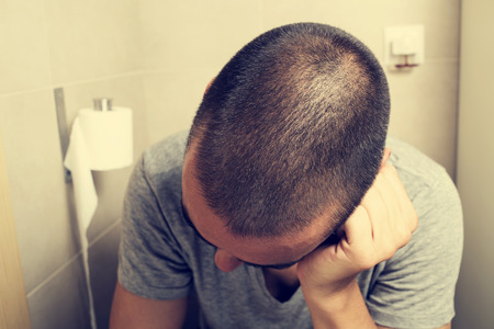public toilet: closeup of a young caucasian man in the toilet sitting in the bowl