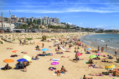 frequented: Tarragona, Spain - August 16, 2015: Sunbathers at Miracle Beach in Tarragona, Spain. Tarragona, in the famous Costa Daurada, has several urban beaches like this, frequented by local
