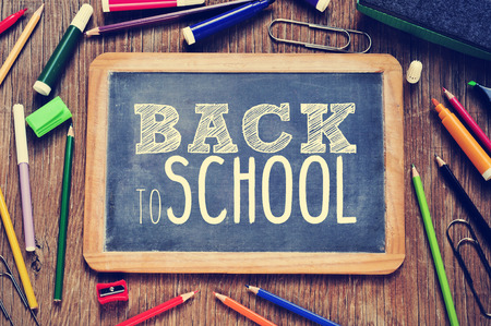 いくつかの鉛筆やマーカーやフィルター効果と、それに書かれて学校に戻るテキストと黒板と素朴な木製のテーブルの高角度ショット