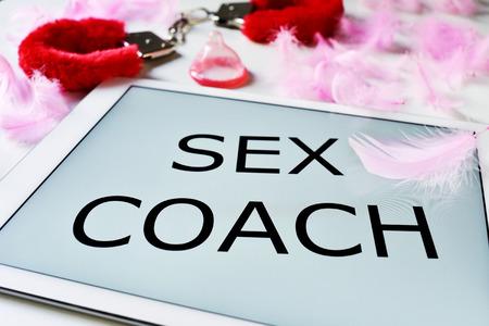 sex: primer plano de un tablet PC con el entrenador el texto del sexo en su pantalla, y un par de esposas esponjosas de color rojo y un condón en un fondo lleno de plumas de color rosa