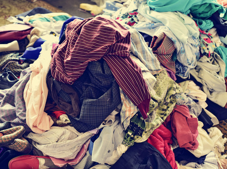 apparel: closeup of a pile of different used clothes on sale in a flea market, with a filter effect