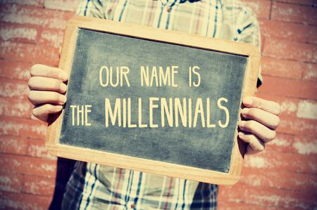 my name is: closeup of a young man holding a chalkboard with text our name is the millennials in front of a brick wall, slight vignette added Stock Photo