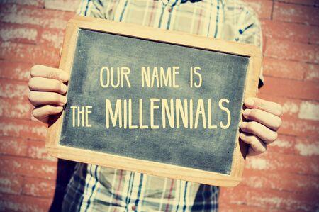 identidad cultural: primer plano de un hombre joven sosteniendo una pizarra con el texto de nuestro nombre es el milenio delante de una pared de ladrillo, ilustraci�n leve a�adi� Foto de archivo