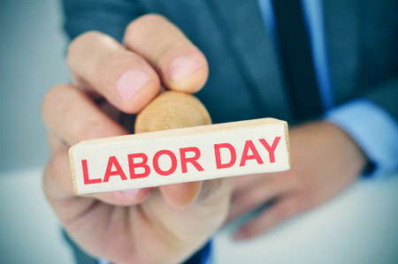 labour: a young caucasian man at his office desk with a rubber stamp with the text labor day Stock Photo