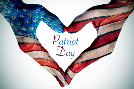 patriot: the text Patriot Day written in the blank space of a heart sign made with the hands of a young woman patterned as the flag of the United States