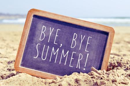 despedida: primer plano de una pizarra con el texto bye, bye verano escrito en ella, en la arena de una playa