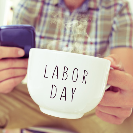 closeup of a young caucasian man with a smartphone and a mug with the text labor day
