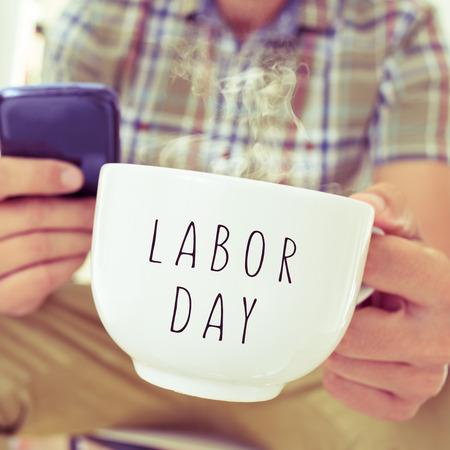 jornada de trabajo: Primer plano de un hombre caucásico joven con un teléfono inteligente y una taza con la jornada laboral de texto