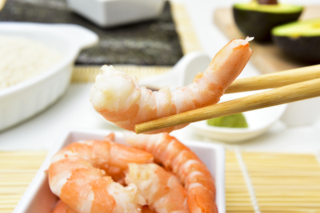 japanese cookery: closeup of a shrimp on chopsticks, and some other ingredients and tools to prepare sushi, such as bamboo mats, sushi rice, or avocado