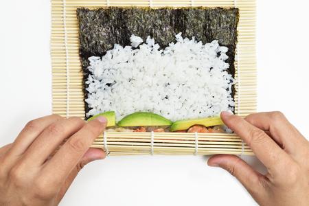 closeup of a young man preparing makizushi, filled with avocado and shrimps