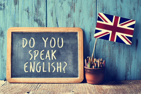 text: a chalkboard with the text do you speak english? written in it, a pot with pencils and the flag of the United Kingdom, on a wooden desk, with a filter effect