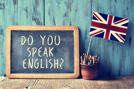 idiomas: una pizarra con el texto habla usted Inglés? escrito en él, una olla con los lápices y la bandera del Reino Unido, en un escritorio de madera, con un efecto de filtro