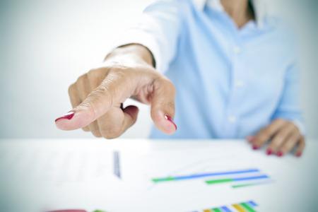 patron: primer plano de una mujer de negocios sentado en su escritorio, lleno de cartas, señalando con su dedo el camino de salida
