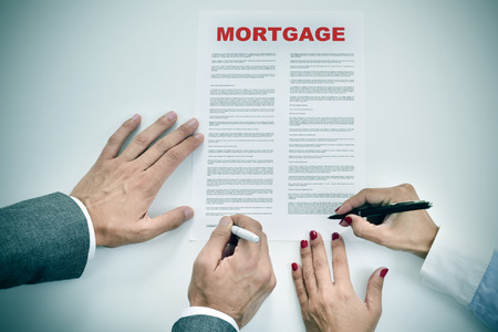 signer: high-angle shot of a man and a woman signing a mortgage loan contract