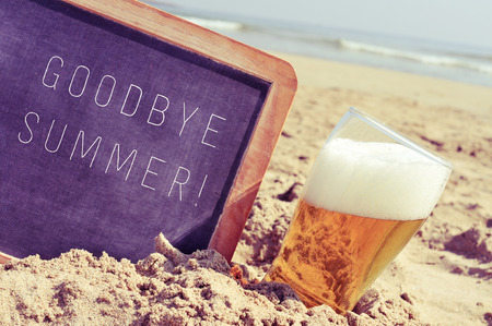 summer drink: closeup of a chalkboard with the text goodbye summer written in it and a glass of beer, on the sand of a beach