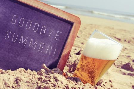 despedida: Primer plano de una pizarra con el verano adi�s texto escrito en ella y un vaso de cerveza, en la arena de una playa