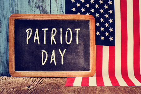 september 11: the text Patriot Day written in a chalkboard and the flag of the United States on a rustic wooden surface