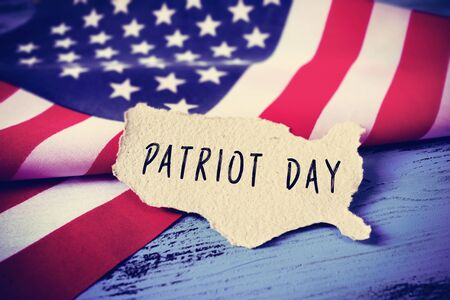 a piece of paper in the shape of the United States with the word Patriot Day written in it, placed on a blue wooden background next to the flag of the United States, vignetted