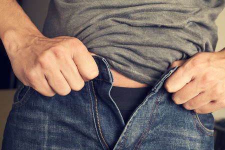 tight fit: closeup of a young man trying to fasten his trousers, because of the weight gain