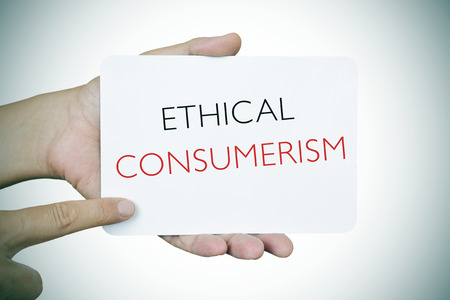 socially: closeup of a young caucasian man pointing his finger at a signboard with the text ethical consumerism, slight vignette added