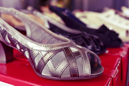 leatherette: closeup of some different woman shoes on sale in a street market, with a filter effect