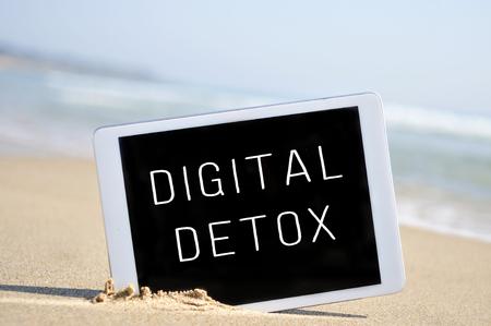 해변의 모래에 배치의 화면에 기록 된 텍스트 디지털 해독과 태블릿 컴퓨터,