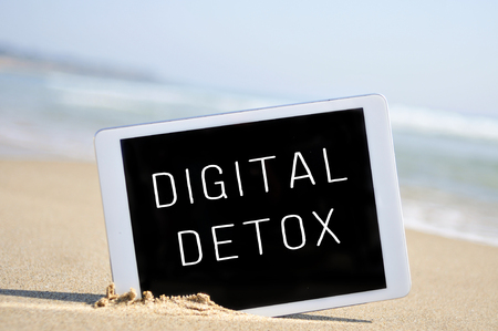 a tablet computer with the text digital detox written in its screen, placed in the sand of a beach