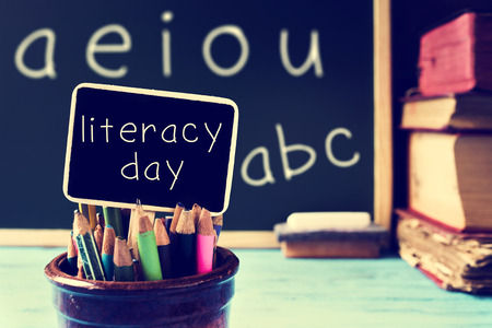 literacy: the text literacy day written in a chalkboard, in a retro and rustic classroom, with a filter effect Stock Photo