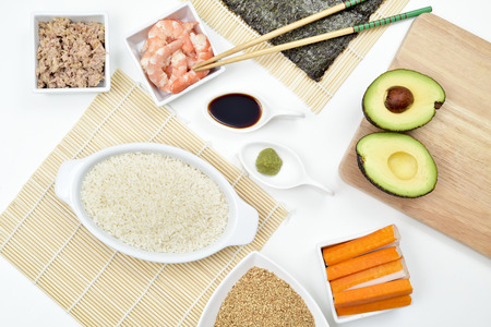 japanese cookery: high-angle shot of a table with some of the ingredients and tools to prepare sushi, such as bamboo mats, sushi rice, tuna, avocado, shrimps or nori sheets Stock Photo