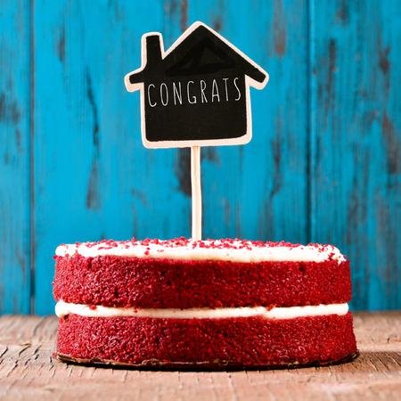 een rood fluwelen taart met een bord in de vorm van een huis met de tekst congrats, op een rustieke blauwe houten oppervlak, met een retro-effect Stockfoto