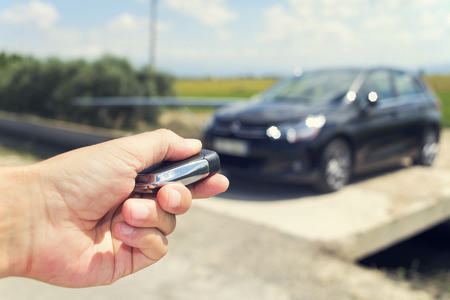 travelling salesman: closeup of a young man unlocking the doors of his car with the control remote key, outdoors, with a filter effect