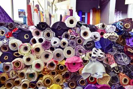 closeup of some different fabric rolls on sale in a street market, with a filter effect