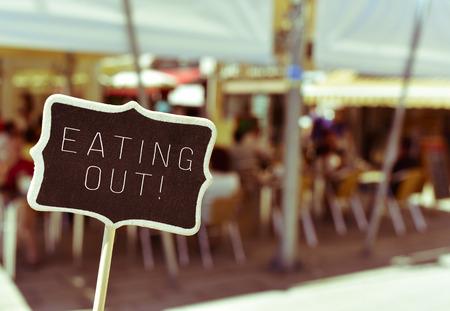 Gros plan d'un tableau avec le texte manger à l'extérieur, sur la terrasse d'un restaurant animé de