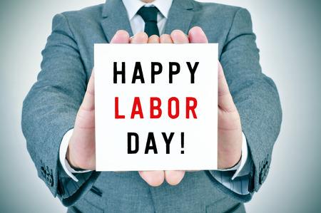 jornada de trabajo: primer plano de un hombre joven en traje mostrando un cartel con el texto del día de trabajo feliz escrito en él Foto de archivo