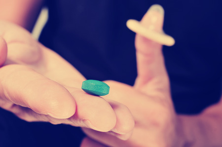impotent: closeup of a young man with a blue pill in one hand and a condom in the other hand, with a filter effect Stock Photo