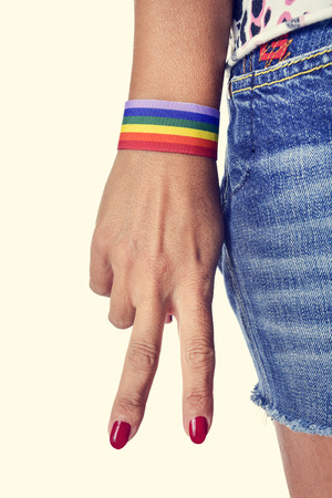 bisexual: closeup of the hand of a young caucasian woman making the V sign, with a bracelet patterned as the rainbow flag Stock Photo