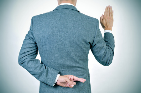 deceiving: a young man in suit swearing an oath, rising his right hand, crosses his fingers in his back Stock Photo