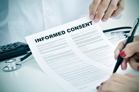 consent: closeup of a young woman patient signing an informed consent at the doctors office Stock Photo