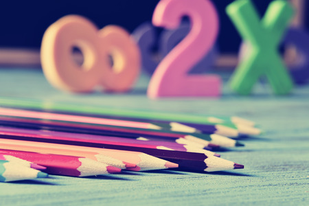 teaching crayons: closeup of a pile of pencil crayons of different colors and some numbers on a blue rustic wooden table in a classroom, with a filter effect Stock Photo