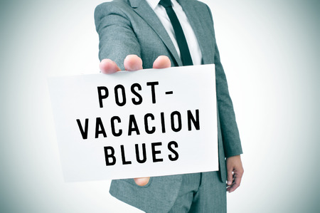 mood: closeup of a young man in suit showing a signboard with the text post-vacation blues written in it, slight vignette added