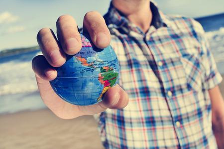 close-up van een jonge blanke man met een wereldbol in zijn hand