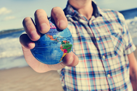 closeup of a young caucasian man with a world globe in his hand